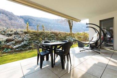 Veranda with garden and outdoor furniture.