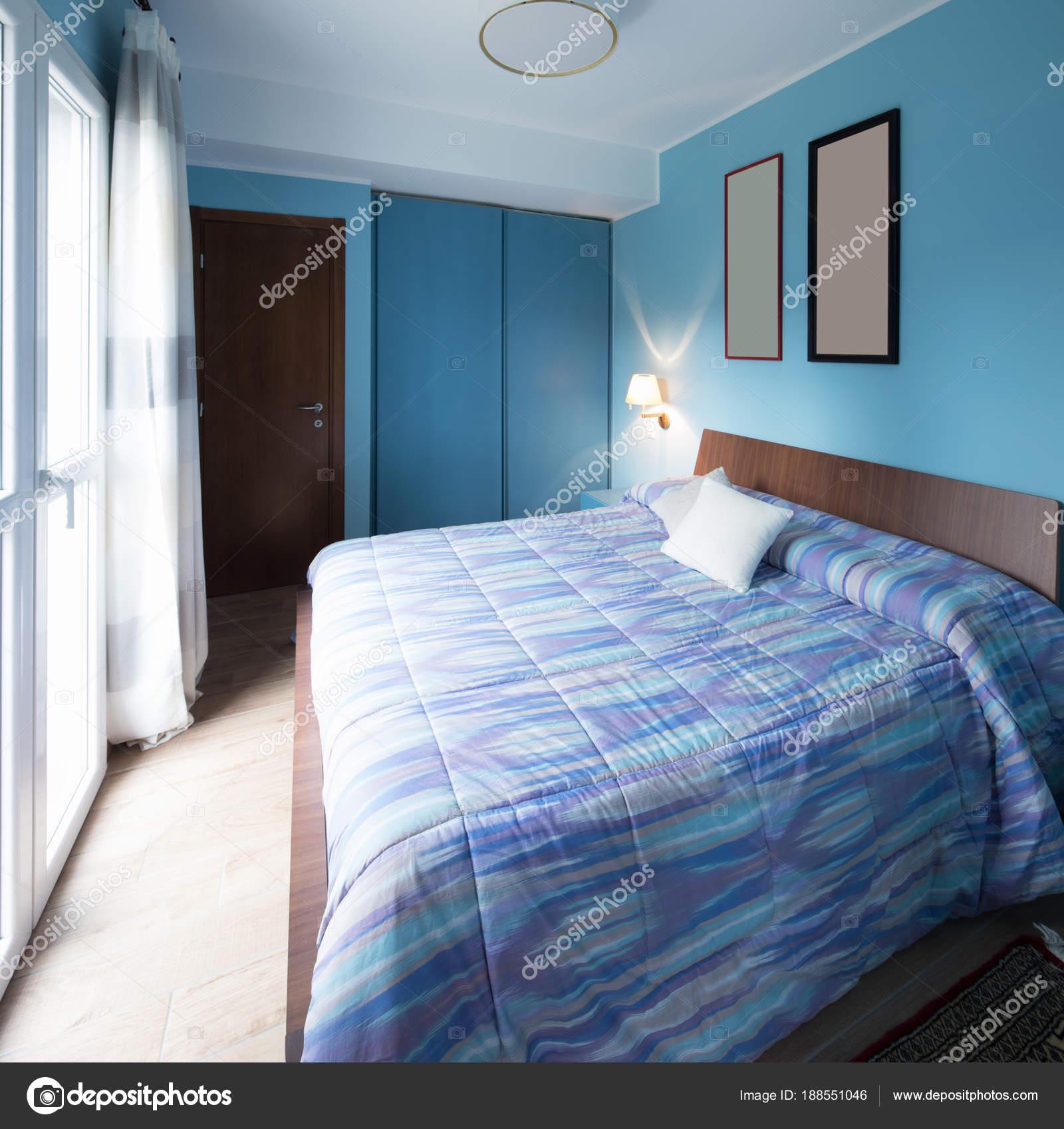 blauwe slaapkamer met frames op de muur stockfoto