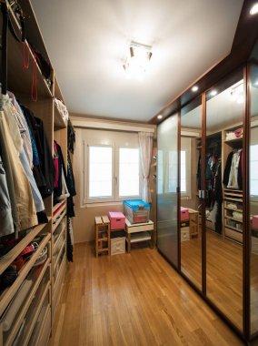 walk-in closet with clothes, parquet floor