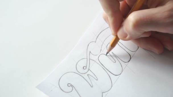 Designer drawing letters with pencil