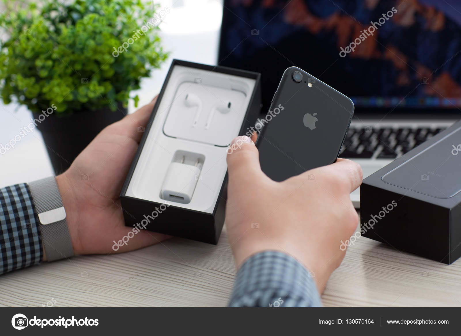 Man Unboxing Iphone 7 Jet Black Onyx Over Macbook Pro Stock