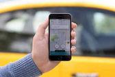 Muž pálivých papriček iphone s aplikací Taxi Uber na obrazovce