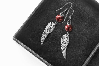 Silver wings shaped drop earrings in black jewel box