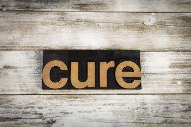 Cure Letterpress Word on Wooden Background