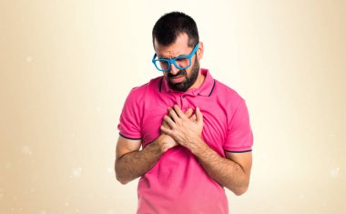 Man in colorful clothes with heart pain on ocher background