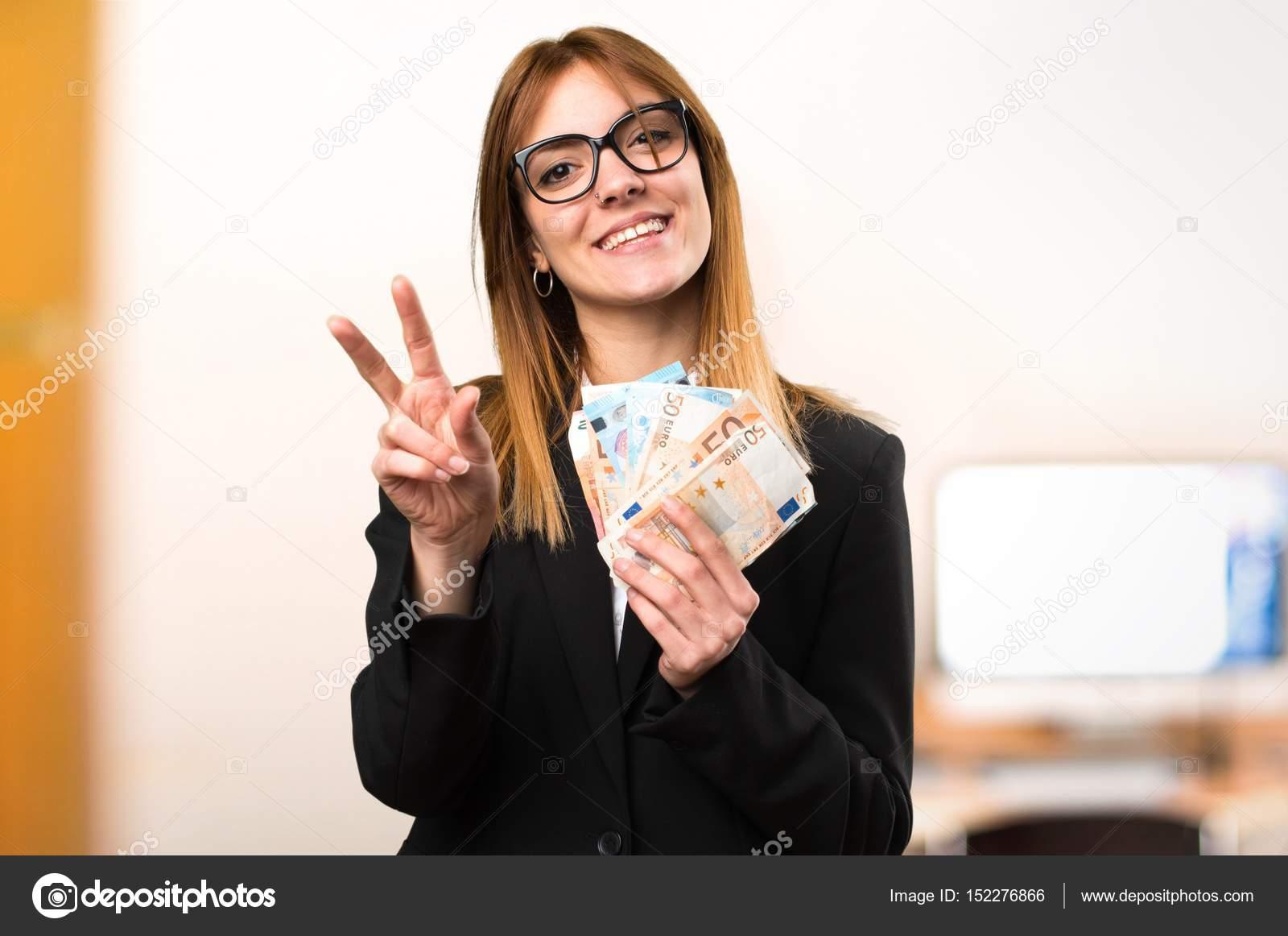 9ed0867cdc720 Mujer de negocios joven tomando un montón de dinero en la oficina de fondo  desenfocado —
