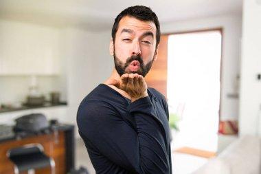 Handsome man with beard sending a kiss inside house