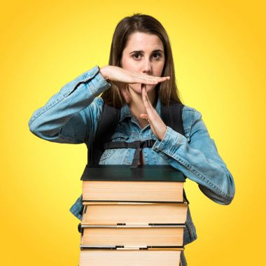 Teen student girl with a lot of books and making time out gestur