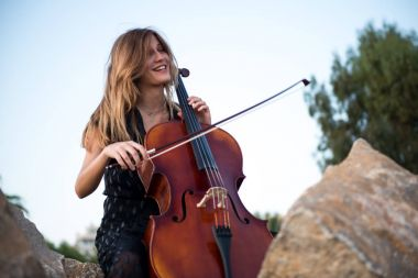 Happy young beautiful girl with her cello on the outside