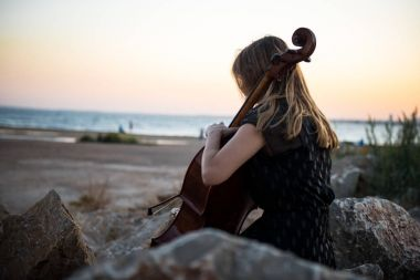 Young beautiful girl with her cello on the outside