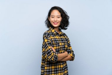 Asian young woman over isolated blue background with arms crossed and looking forward