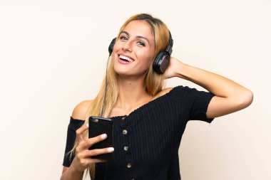Young blonde woman listening music with a mobile over isolated background