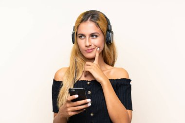 Young blonde woman listening music with a mobile and thinking over isolated background