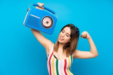 Young woman in summer holidays over blue background holding a radio