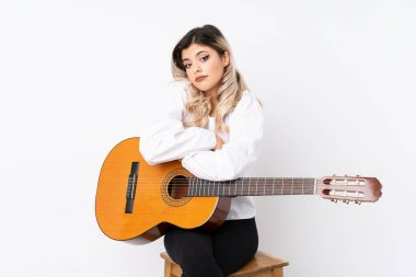 Teenager girl with guitar over isolated white background making doubts gesture while lifting the shoulders