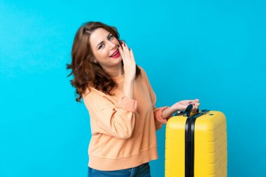 Traveler woman with suitcase over isolated blue background whispering something