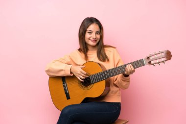 Young brunette girl with guitar over isolated pink background