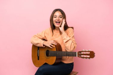Young brunette girl with guitar over isolated pink background shouting with mouth wide open