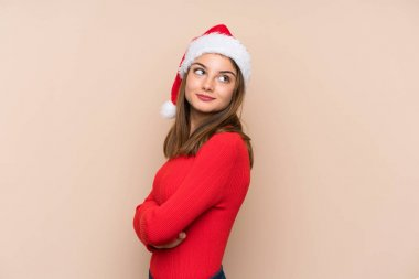 Young girl with christmas hat over isolated background laughing