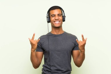 Young handsome man listening music with a mobile over isolated green wall