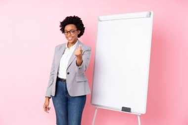 African american business woman giving a presentation on white board over isolated pink background inviting to come with hand. Happy that you came