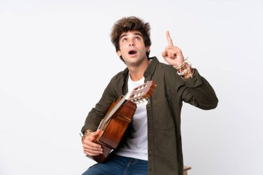 Young caucasian man with guitar over isolated white background pointing with the index finger a great idea