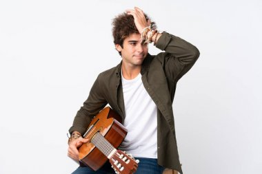 Young caucasian man with guitar over isolated white background having doubts with confuse face expression