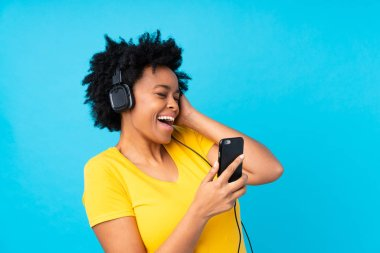 Young african american woman listening music with a mobile over