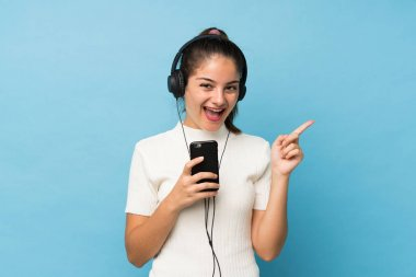 Young brunette girl over isolated blue background using the mobile with headphones and singing