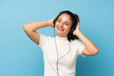Young brunette girl over isolated blue background using the mobile with headphones