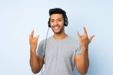 Young handsome man over isolated background using the mobile with headphones and dancing