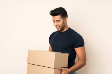 Young handsome man over isolated background holding a box to move it to another site