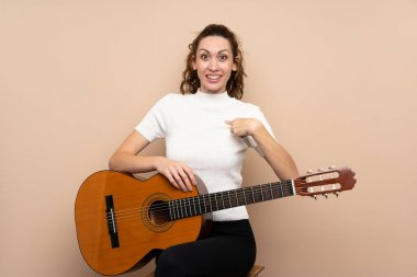Young woman with guitar over isolated background with surprise facial expression