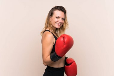 Blonde sport woman over isolated background with boxing gloves