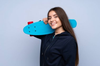 Young woman over isolated blue background with skate