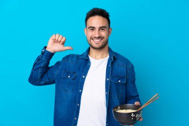 Young handsome man over isolated blue background proud and self-satisfied while holding a bowl of noodles with chopsticks