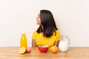 Young brunette girl having breakfast milk looking to the side