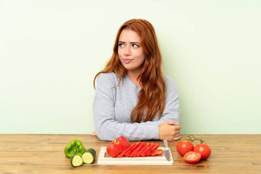 Teenager redhead girl with vegetables in a table standing and looking to the side