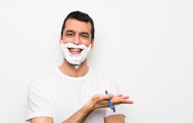 Man shaving his beard over isolated white background presenting an idea while looking smiling towards