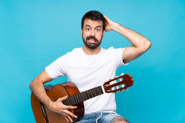 Young man with guitar over isolated blue background frustrated and takes hands on head