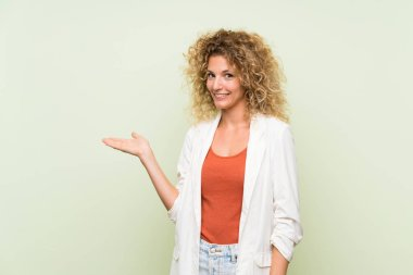 Young blonde woman with curly hair over isolated green background holding copyspace imaginary on the palm