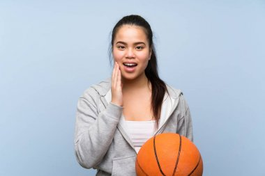 Young Asian girl playing basketball over isolated background with surprise and shocked facial expression