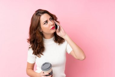 Young Russian woman over isolated pink background holding coffee to take away and a mobile