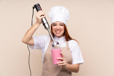 Redhead teenager girl using hand blender over isolated background