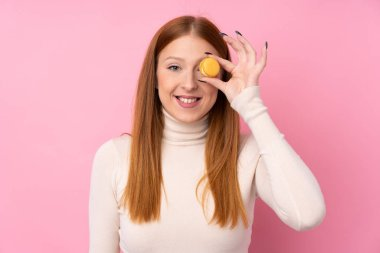 Young redhead woman over isolated pink background holding colorful French macarons