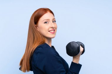 Young redhead sport woman over isolated blue background making weightlifting