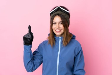 Young skier woman over isolated pink background pointing with the index finger a great idea