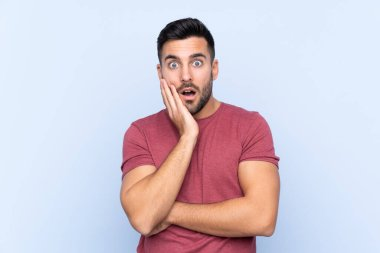 Young handsome man with beard over isolated blue background surprised and shocked while looking right