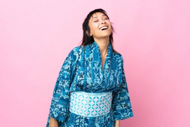 Young woman wearing kimono over isolated blue background laughing