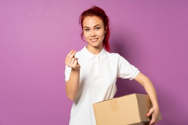 Teenager delivery girl isolated on purple background making money gesture
